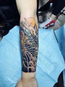 木材商人王先生手臂處的彩繪錦鯉花臂紋身圖案圖片